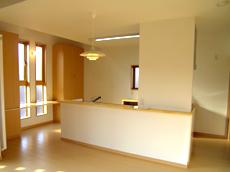I型キッチンを中央に配し、アイランド型にすることで、動きやすい動線と広々としたキッチンに。 窓際は奥様の書斎と収納を。