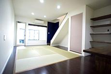 玄関から上がったリビング。 両サイドの窓が作れないため、玄関兼ガレージから明かりを取るように工夫。 階段隣の壁には仏壇を置くスペースを造り、プリーツスクリーンを下げて、リビングに違和感の無い様にしました。
