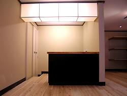 杉板で作ったレジカウンターです。 上には、和紙を貼った手作りの照明器具を天井につけました。 柔らかい光がいいですよね。