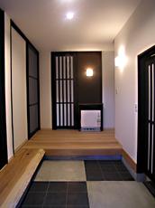 玄関ドアを開ける。タイルとモルタルで市松模様に。土間の感覚を組み込んだ。