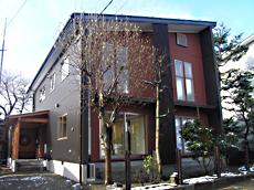 建物正面。 ブラックとベンガラ色の箱型の外観。