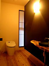 トイレは、スリット窓に障子、杉板の表面を焼き、自然な表情を浮かばせた手洗いカウンター。 'ゆとりのある空間'