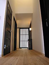 廊下。 ダークな建具にナチュラルな無垢の杉板を床材に選んだ。優しい肌触りが喜ばれた。