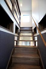 階段。1階天井裏空間を利用して、階段の両脇に本棚を造りました。ここに座って本を手に取るのも、意外と落ち着くかも?!