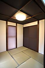 ダークな色の格子天井や襖戸、和紙調のプリーツスクリーンが、落ち着いた空間に。